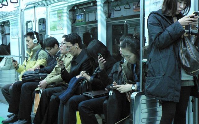 Lidé zírají na svá mobilní zařízení