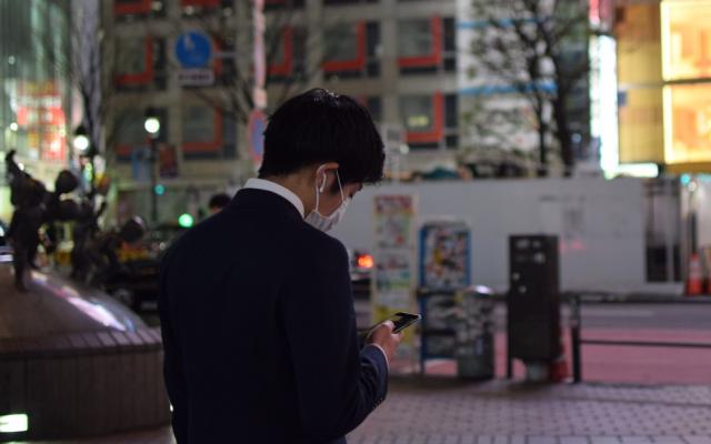 Muž se dívá do mobilu, zatímco čeká na zelenou u přechodu. Šibuja, Tokio.